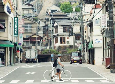 市街地。駅から続く商店街、線路の向こうに続く坂道。