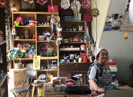 折り紙が並ぶ店内と座る信さん