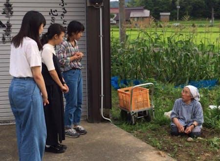 畑で作業をしているお母さんに話を聞く村・留学参加者