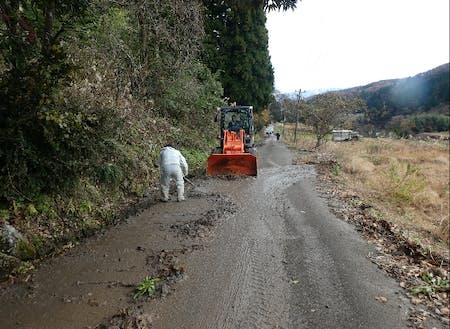 雪解け後に道路に流れ出てきた泥を清掃する様子