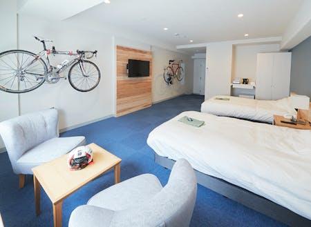 ゆったり広々とした客室。テレビボード・ヘッドボードは村産材を使用。全室サイクリングラック完備。