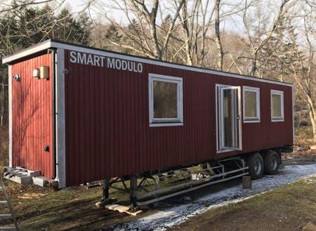 """冬に設置した移動可能な木造建築""""Smart Modulo""""。宿泊や飲食もできるテレワーク拠点として利用可能。ここに太陽光発電システムやウッドデッキ等を整備していく。断熱がしっかりとしていて、冬の森の中でも快適に過ごすことができた。"""