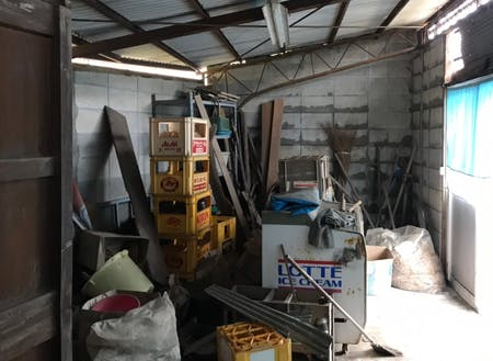 自転車やさんだった場所は物置に。手前の木の棚の中には当時の工具や部品が並んでいた。