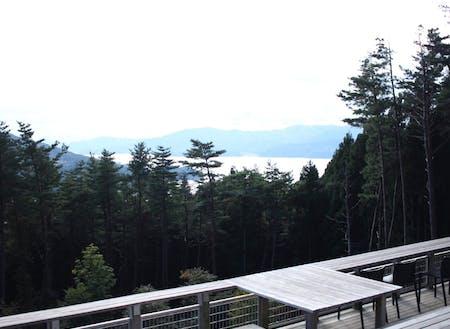 箱根山テラスがあるのは、陸前高田市の広田半島。その付け根にある「箱根山」という低山、木漏れ日のさす細い坂道を登っていくと現れる広々としたデッキからは、森林の間から広田湾を見下ろすことができます。