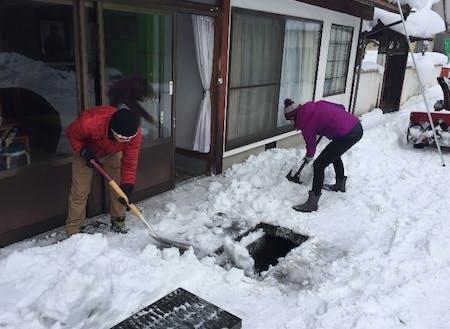 積もった雪を流雪溝に流す様子