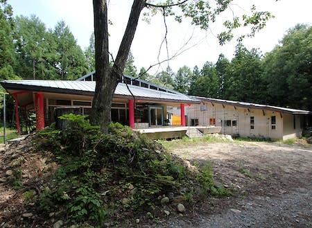 ホテルや民宿から離れた森の中に立地する鉄骨造280坪の建物