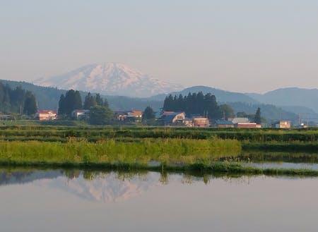 田植え前の田に映る鳥海山と集落。こんな風景を僕らは守れるだろうか。