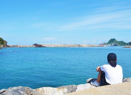 海辺で若者はぼーっと海と空を眺める
