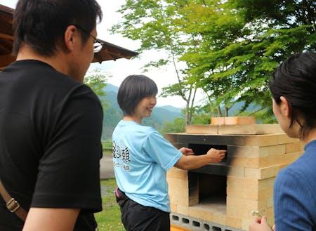 魚梁瀬地区のキャンプ場で、ピザ窯について説明している西尾さん。西尾さんは他にも魚梁瀬ダムでのSUPなど、魚梁瀬地区にある資源をいかした新しいアクティビティにチャレンジしています。