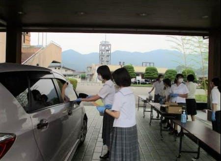 コロナ禍で町内飲食店を支援するために、高校生が発案したドライブスルー形式の助け合いマルシェの様子